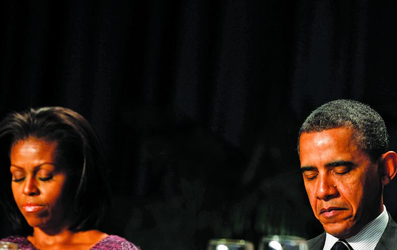 LARRY DOWNING / REUTERS Are you there, God? The Obamas at the National Prayer Breakfast, February 2012.