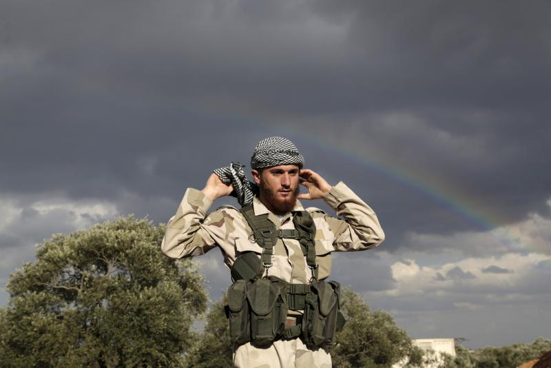 A rainbow is seen over an Islamic Ahrar al-Sham fighter on the frontline of Idlib city in northern Syria, where they announced a battle to liberate the city from forces loyal to Syria's president Bashar Al-Assad, March 20, 2015.