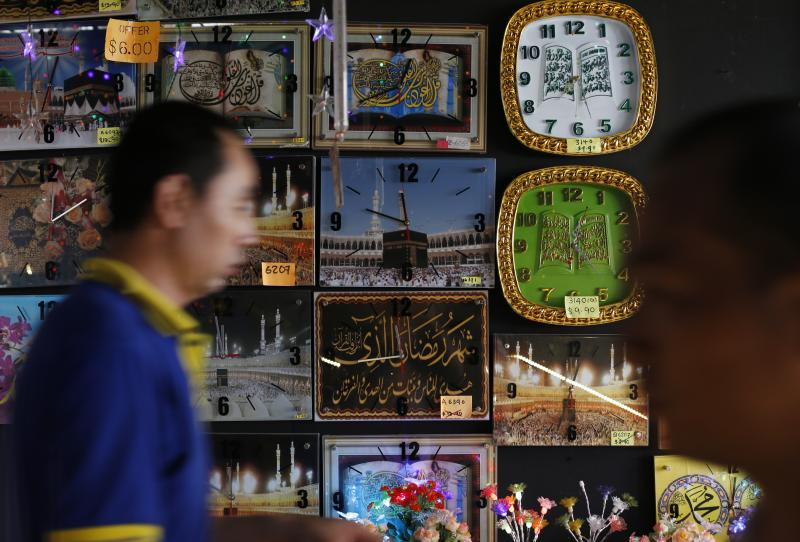 Edgar Su / Reuters People pass a stall selling clocks, depicting religious verses and pilgrims at the Hajj, at a Hari Raya bazaar, on the eve of Eid al-Fitr, in Singapore July 27, 2014.