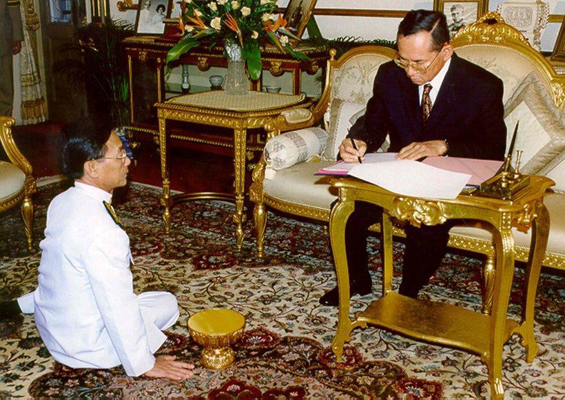كان الملك الراحل يُعامل وكأنه إله. في الصورة، في ٤ نوفمبر ١٩٩٧، الملك يوقّع المرسوم الملكي بالموافقة على الحكومة الجديدة برئاسة شوان ليك باي، الجالس أمام الملك على الأرض