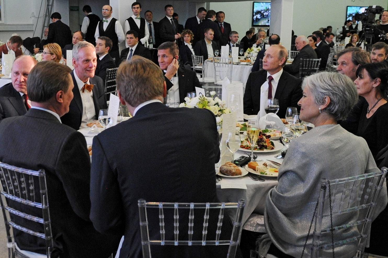 """الجنرال فلين جالساً إلى يمين الرئيس بوتين في احتفال بذكرى مرور 10 سنوات على تأسيس تلفزيون """"روسيا اليوم""""."""