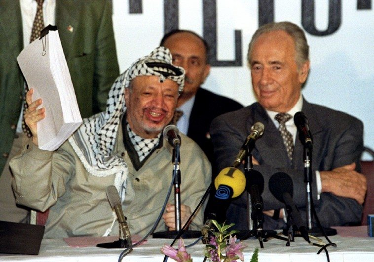 PLO chairman Yasser Arafat holds the second phase of the Oslo peace accords after the initialling of..